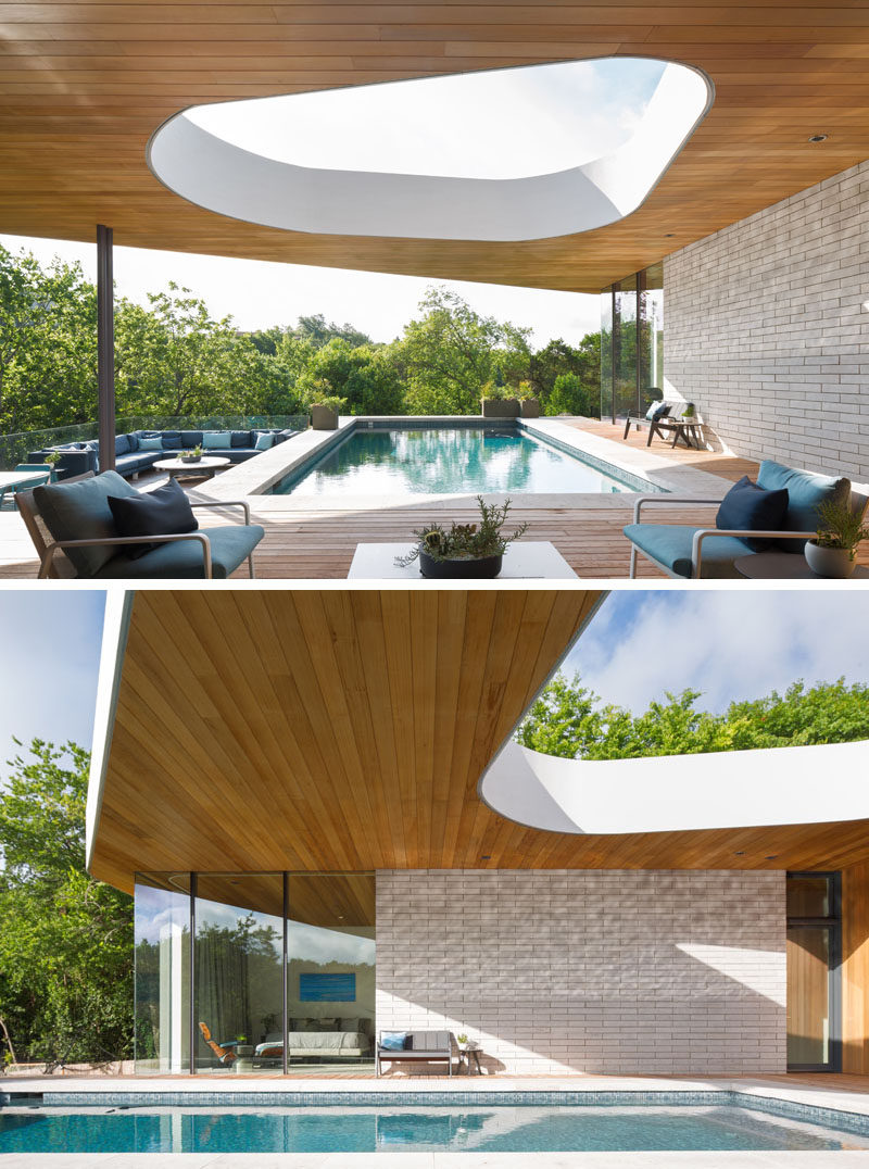 This modern house has a large outdoor area with a cut-out in the roof, a swimming pool and wood deck, and an outdoor lounge area. #SwimmingPool #Deck #OutdoorLounge