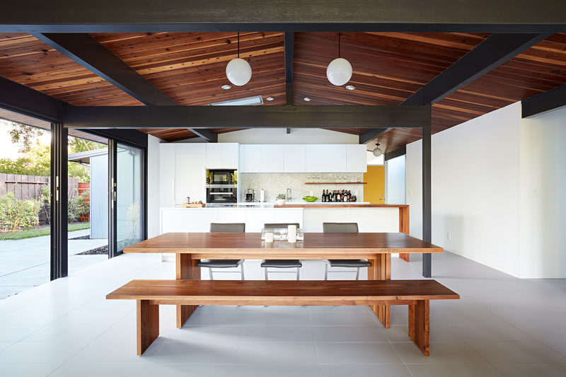 In this open plan dining room, a wood dining table complements the exposed stained wood ceiling above. #DiningTable #OpenPlanInterior #WoodCeiling