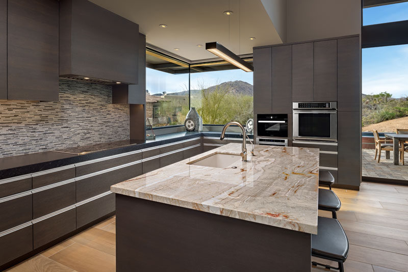 In the this modern kitchen, dark cabinetry is combined with earth-tone tiles and stone countertops to create a contemporary appearance. #ModernKitchen #DarkCabinetry