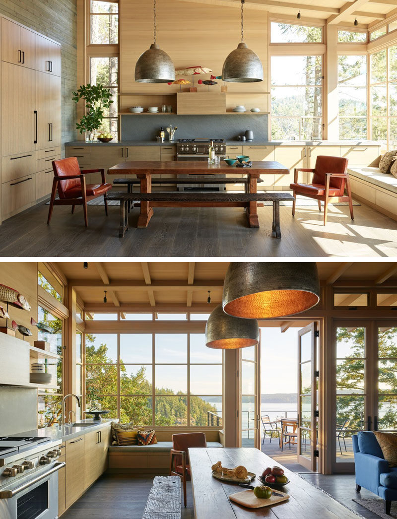 Light wood, a sloped ceiling, and plenty of windows, ensure that this kitchen is bright and welcoming. There's a built-in window seat for taking in the views, while doors connect the interior with the deck. #KitchenDesign #WindowSeat #WoodKitchen #Windows