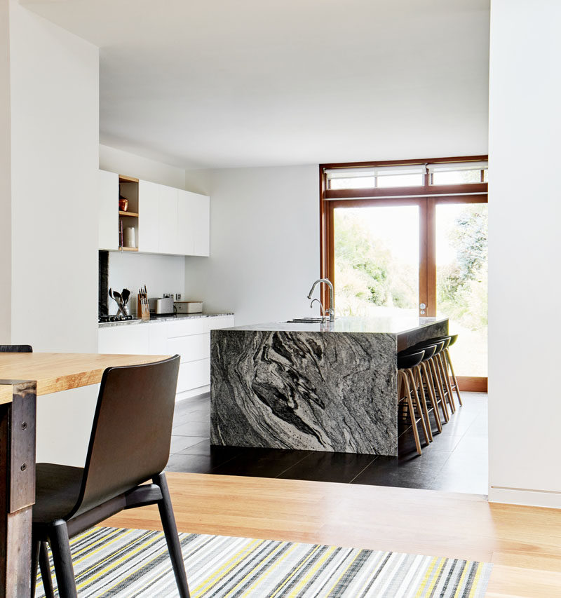 This modern kitchen has a large grey/black island with seating, while wood accents and door frames add a natural touch to the interior. #Kitchen #ModernKitchen #KitchenDesign