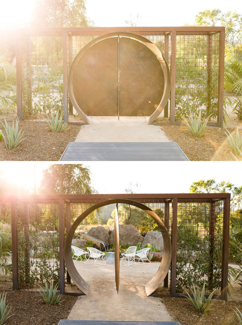 In this modern backyard, there's a circular steel doorway that opens to a peaceful sitting area. #Landscaping #LandscapeDesign