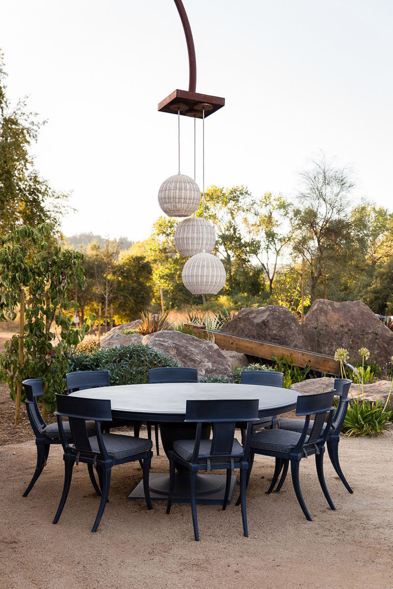 This alfresco dining area has three pendant lights hanging above a round dining table. #OutdoorDining #AlfrescoDining