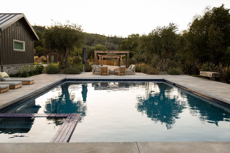 This swimming pool with a space is surrounded by a deck with a variety of seating options. #SwimmingPool