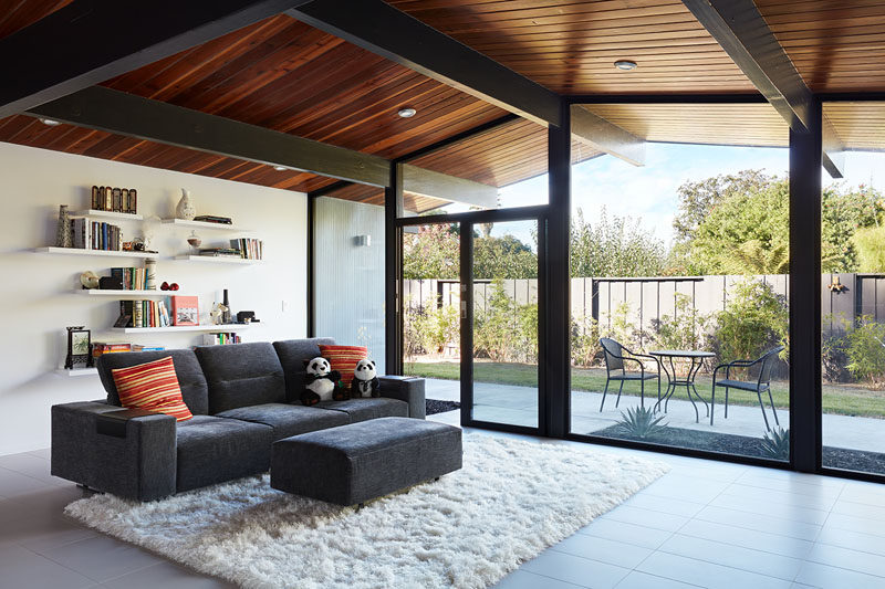This reconfigured great room with new full height windows and sliding glass doors blends the indoors with the outdoors. #LivingRoom #Windows #ModernInterior