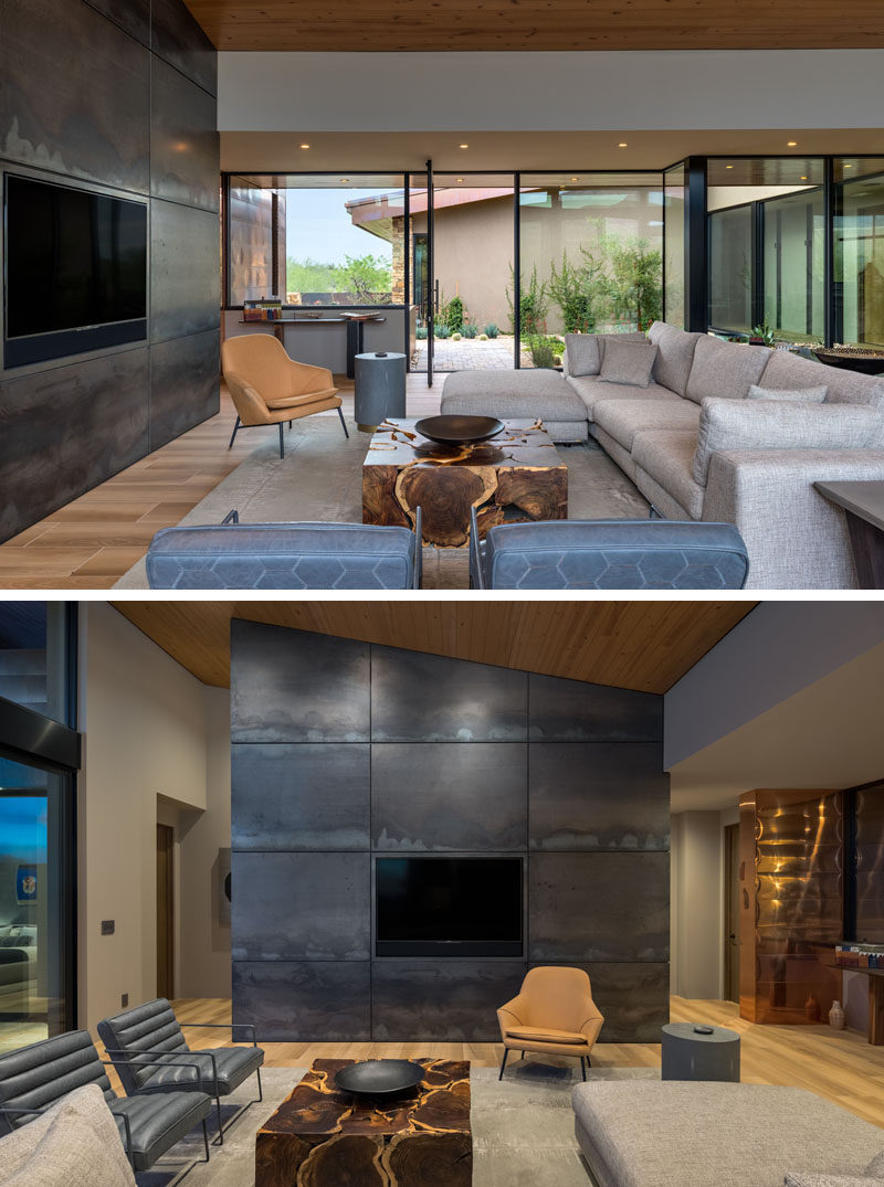 The front door of this modern house opens to the living room, that features a large steel accent wall. Walls of glass provide daylight to the interior and frame the garden and views outside. #ModernLivingRoom #SteelAccentWall #GlassWalls