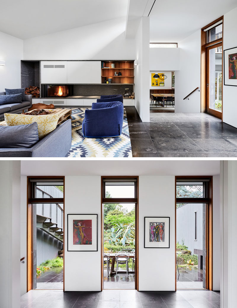 In this modern living room, there's a fireplace with built-in wood storage and wood bookshelves, while three doors adjacent to the sitting area, open up to the landscaped courtyard where there's an outdoor dining area. #ModernLivingRoom #LivingRoom #OutdoorDining