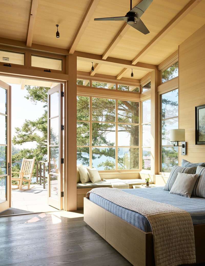 This contemporary master bedroom has a built-in window seat, a high sloped ceiling, and access to a deck. #BedroomDesign #WindowSeat
