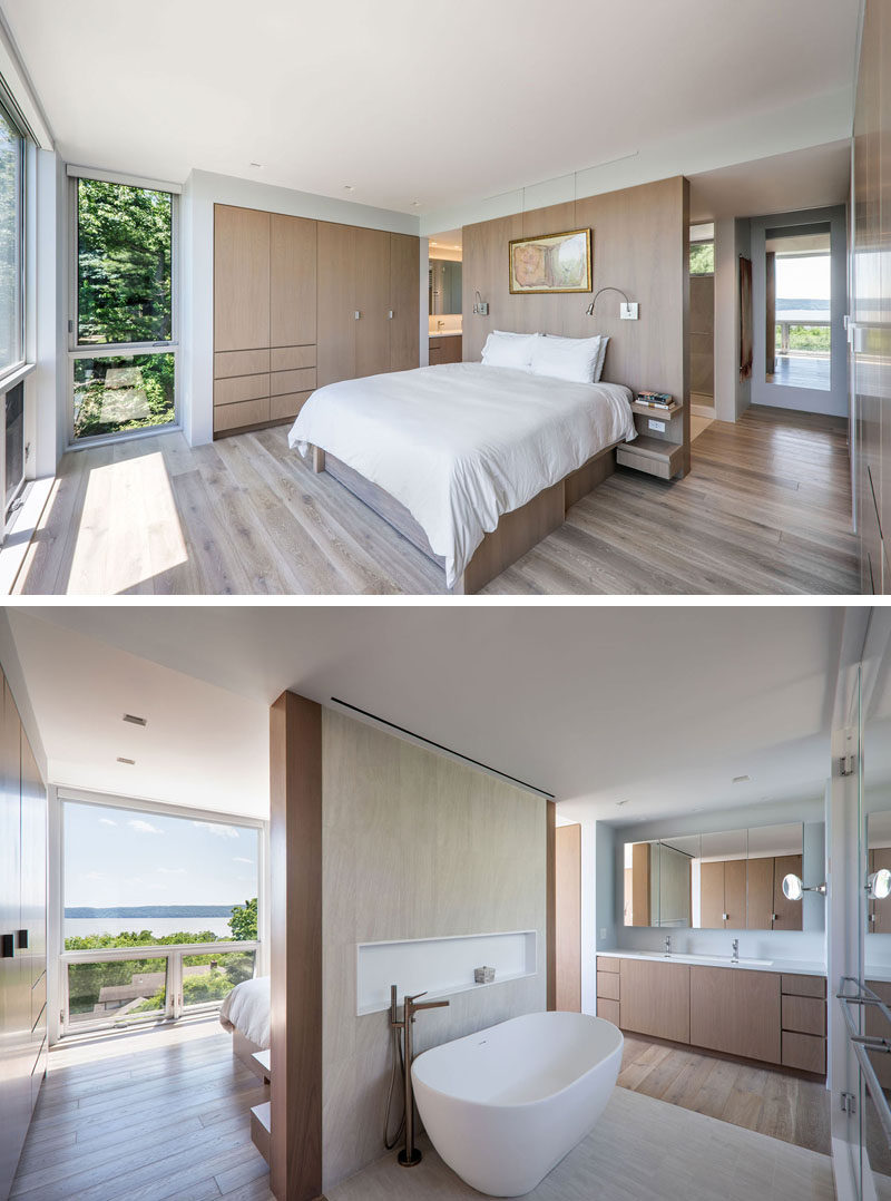 This modern master suite has the bed positioned to take advantage of the views, and an open bathroom with a freestanding bathtub and a walk-in shower. #MasterSuite #MasterBathroom #MasterBedroom #ModernBedroom