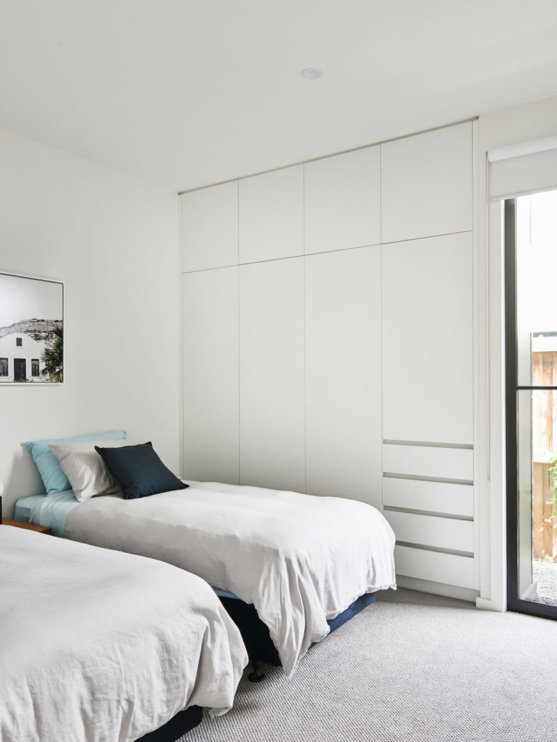 This modern bedroom has a minimal design with a built-in closet that takes up one wall. #Closet #Bedroom