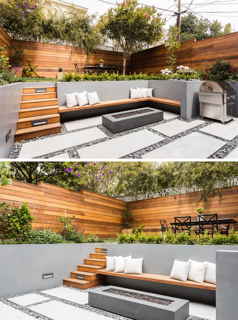 On the lower level of this modern backyard, there's custom-colored concrete walls with a built-in wood bench that fits into the corner and sits beside the firepit. On the ground, pavers are surrounded by riverstone, while wood stairs lead to the upper level with an area for alfresco dining. #ModernLandscaping #ModernBackyard #MultiLevelBackyard