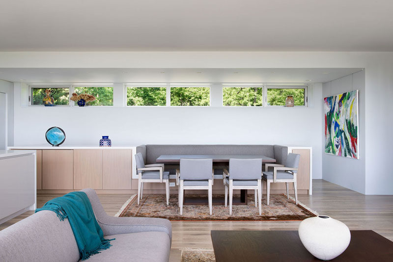The dining area of this modern house has banquette seating that's been built into the sideboard design, while clerestory windows add a touch of natural light. #DiningRoom #BanquetteSeating #ModernInterior