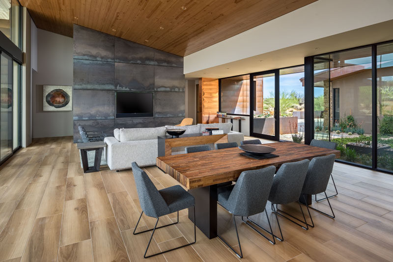 A sloped wood ceiling helps to keep the interior of this modern house feeling open and bright. #WoodCeiling #SteelAccentWall #DiningRoom