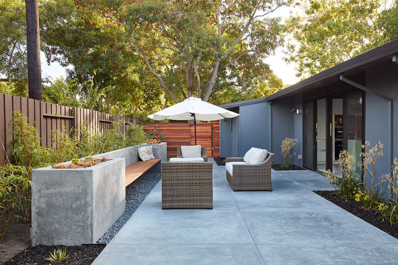 This modern patio area has a built-in wood and concrete bench, that features planters on either end. #Landscaping #OutdoorSeating #Patio