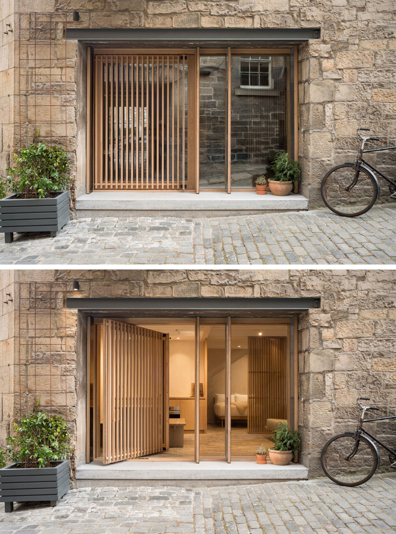 The original opening of this old blacksmiths shop was repurposed with deep mullioned windows and a wood screened pivot door, providing both privacy and views of the courtyard. #PivotingDoor #WoodSlatDoor #Windows
