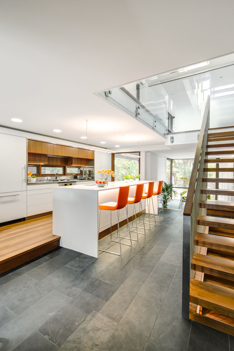 In this modern kitchen, wood cabinets contrast the surrounding white cabinetry, and a large island offers bar height seating. #Kitchen #ModernKitchen