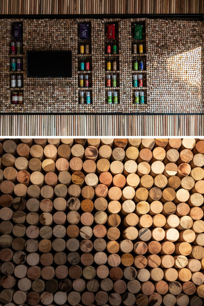 Small wood discs have been tightly packed on the wall of this modern retail store, changing patterns and colors, with openings left for display shelves. #RetailStore #WoodWall