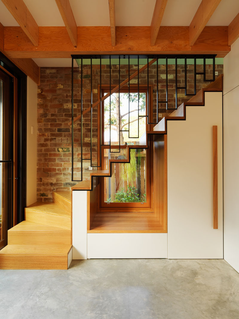 This modern house has a cut-out underneath the stairs to allow the light from the window to flow through to the interior. #Stairs #InteriorDesign #Window