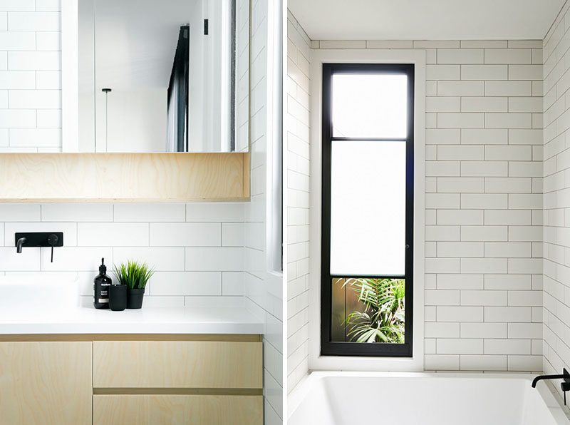 In this modern bathroom, simple white tiles cover the walls, while a built-in bathtub sits below the window, and the vanity features plywood and a white countertop. #ModernBathroom #WhiteBathroom