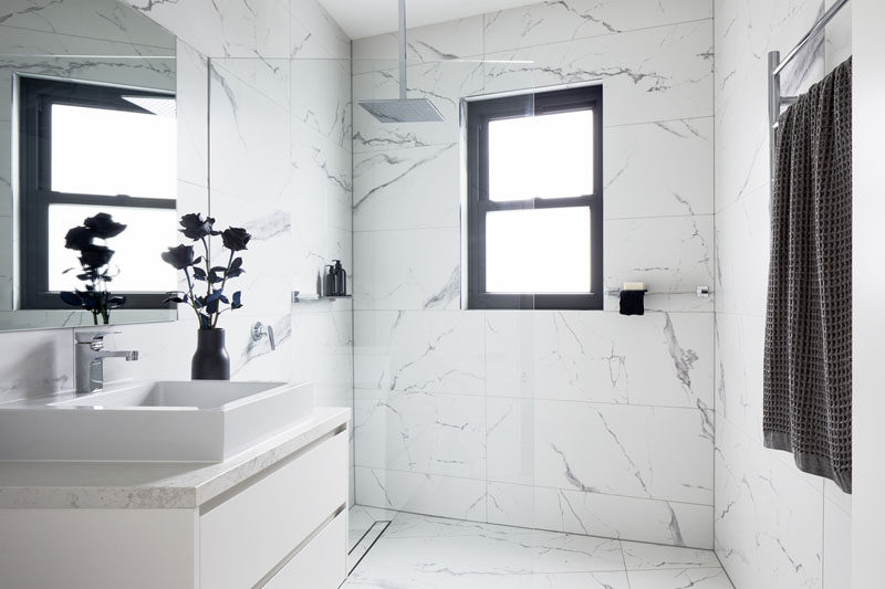 The frameless glass shower screen in this modern bathroom allows the natural light from the window to flow throughout the room. #BathroomDesign #WhiteBathroom