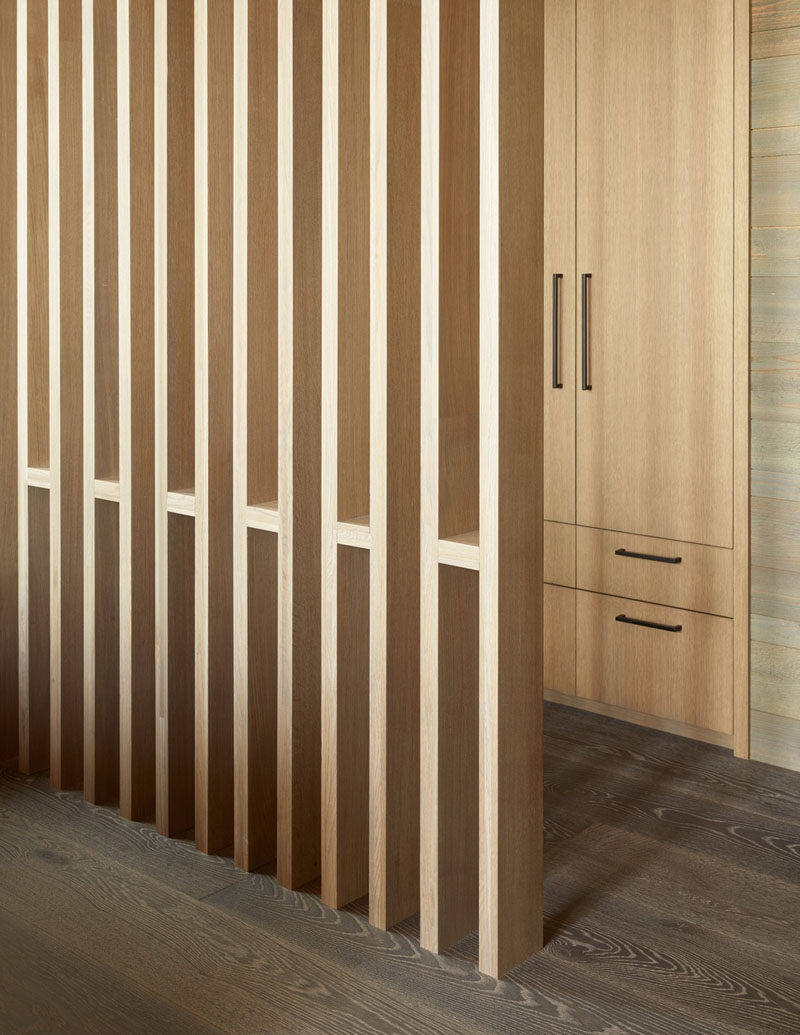 This master bedroom has a simple, contemporary room divider that separates the closet from the sleeping area. #RoomDivider #WoodScreen
