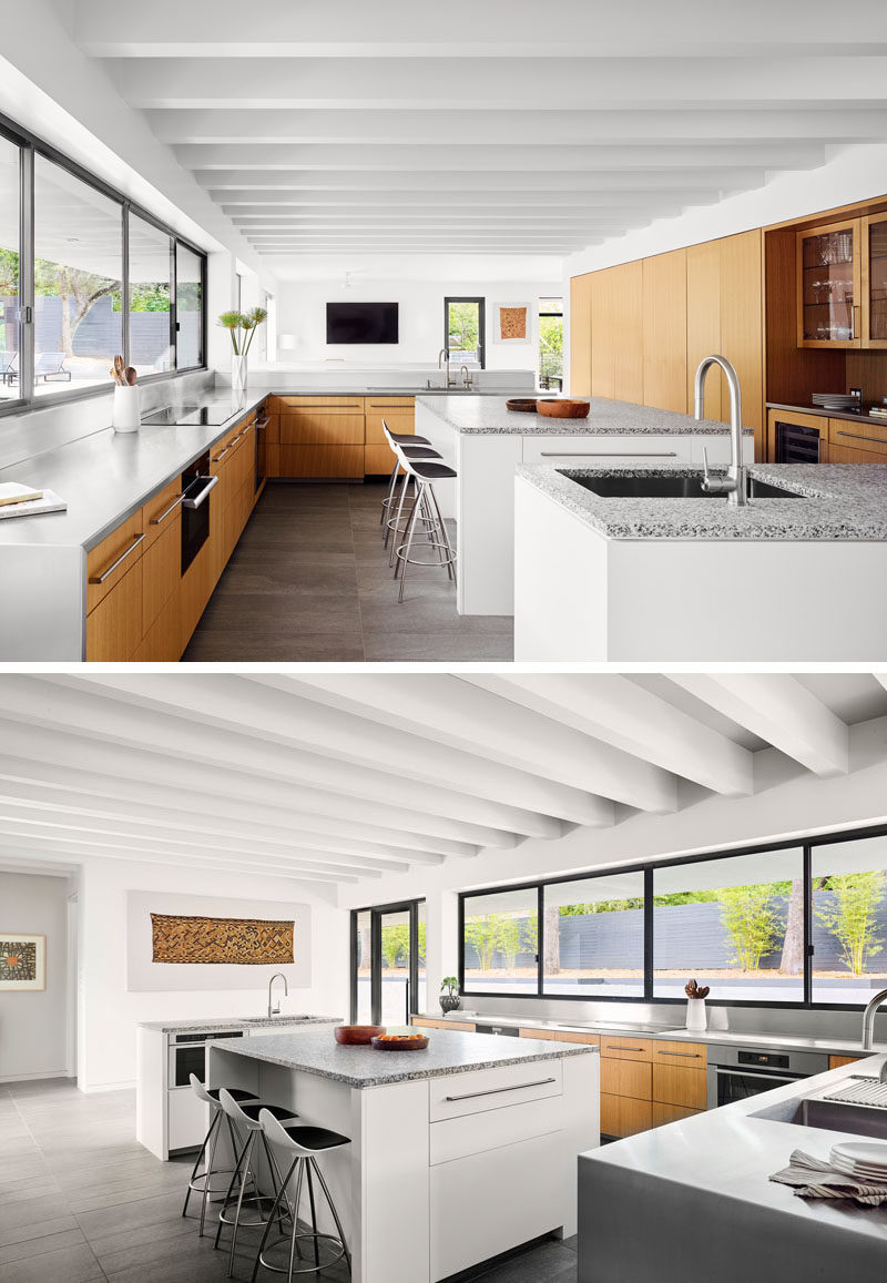 This modern and large kitchen has countertop-height serving windows that open out onto a pool terrace and entertaining area. #Kitchen #ModernKitchen #KitchenDesign