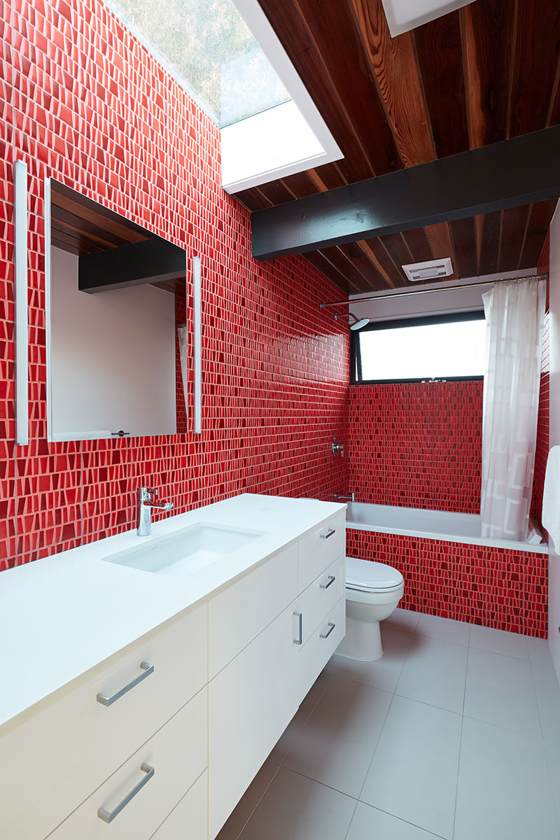 In this modern bathroom, bold bright red tiles cover the walls and bath surround, and contrast the white vanity. A skylight above the vanity helps to keep the room bright. #Bathroom #RedBathroom #BoldBathroom