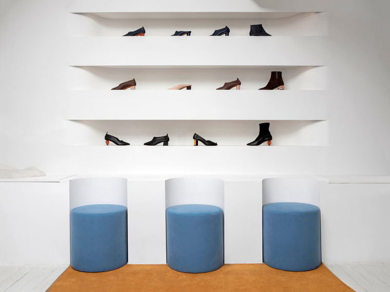 As part of the design of this modern showroom, the white benches around the edges of the interior have curved sections cut out to house the soft, dusty blue seats. #Seating #Showroom #RetailDesign