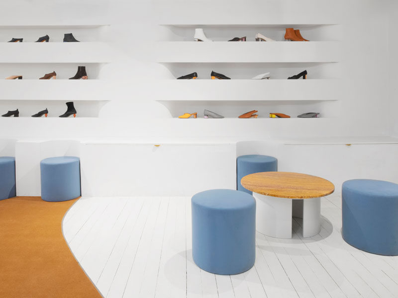 In this showroom, the seats seamlessly fit in with the white benches, which also offer additional room for storage, while above, the soft, curved lines of the shelving tuck into the wall to create a visual pattern of smoothed rectangles. #Showroom #InteriorDesign