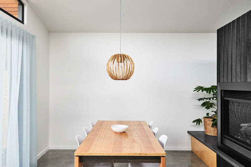 In this minimalist dining room, a single wood pendant light hangs above the dining table that's surrounded by white chairs. #DiningRoom