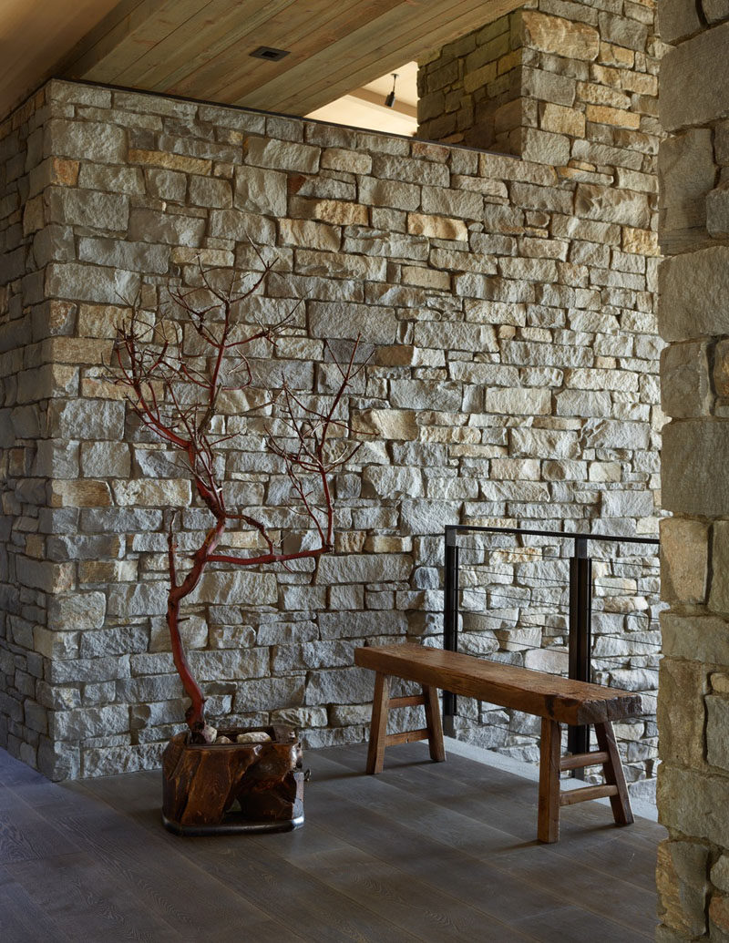 A pair of thick stone walls in this house separates the main level into public and private realms and flanks a central stone staircase. #StoneWall #Entryway