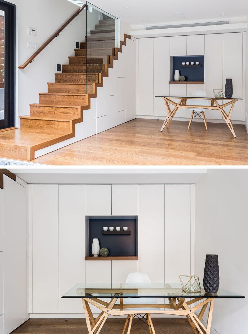 This modern bonus room has been set up as a home office, with floor-to-ceiling minimalist white cabinets and a hidden powder room under the stairs. #BonusRoom #HomeOffice #Stairs #WhiteCabinets