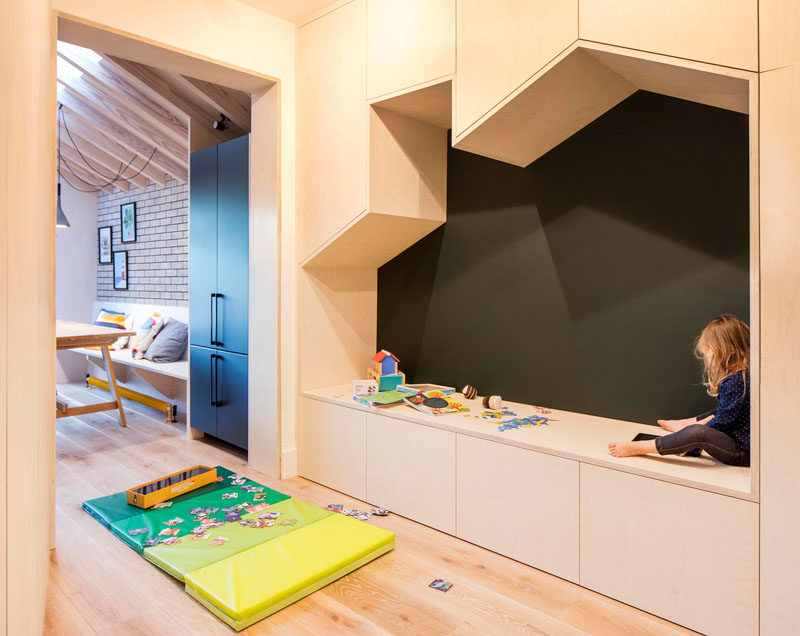 Adjacent to the dining area int his updated home by Woodrow Architects, is a small playroom with a built-in seating nook in the shape of a house, that's surrounded by storage cabinets. #BuiltInSeating #PlayRoom Visit Woodrow Architect's website here > https://www.wdrw.co.uk