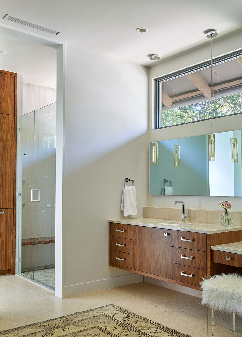 In this master bathroom, light colored walls and floors have been combined with wood cabinetry for a contemporary appearance. #Bathroom #MasterBathroom