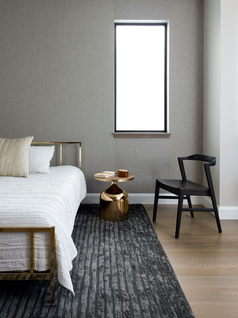 In this modern bedroom, a grey rug complements the grey accent wall, while the black chair ties in with the window frame, and the gold accents add a metallic touch. #ModernBedroom #BedroomDesign
