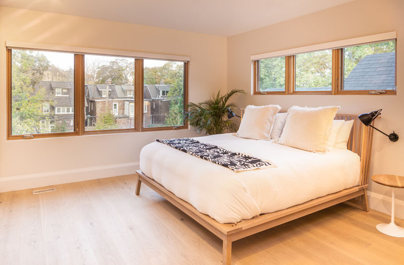 In this bedroom, rows of wood-framed windows fill the minimally furnished room with an abundance of natural light. #Bedroom #Windows