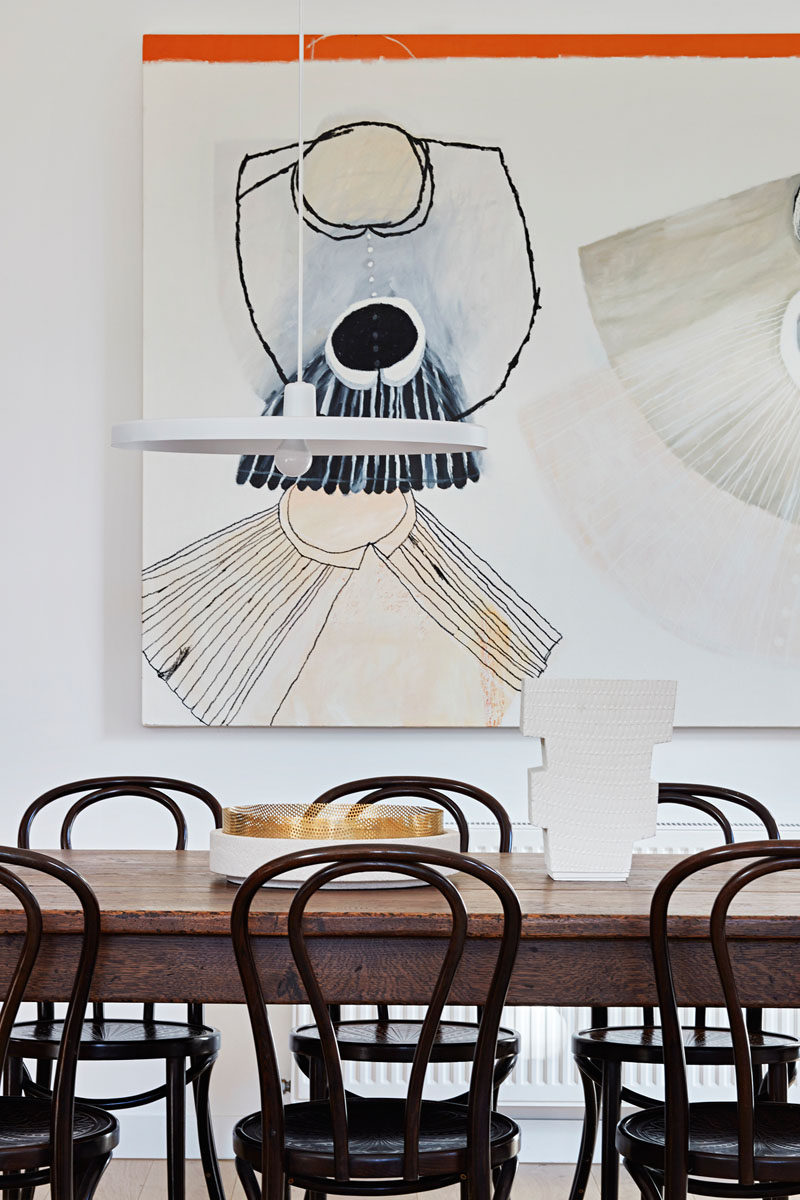 In this contemporary dining room, a large piece of art hangs on the wall, while a minimalist white pendant lamp hangs above the dark wood table and chairs. #DiningRoom