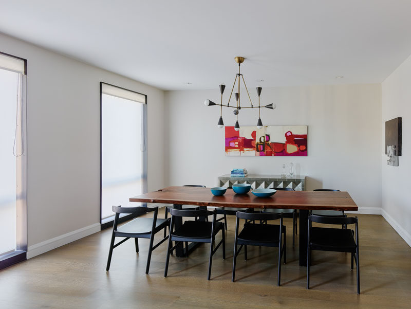 In this contemporary dining room, a large wood dining table sitting below a minimalist chandelier, and artwork on the walls. #DiningRoom