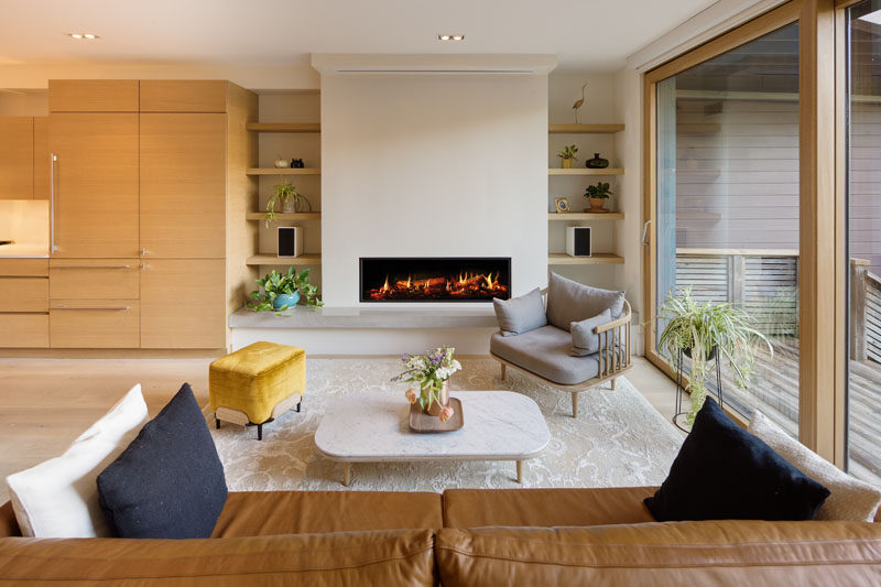 This living room is focused on the fireplace that has built-in shelving on either side. A large 3-panel lift and slide glass door opens the living room to the backyard. #LivingRoom #Fireplace #Shelving