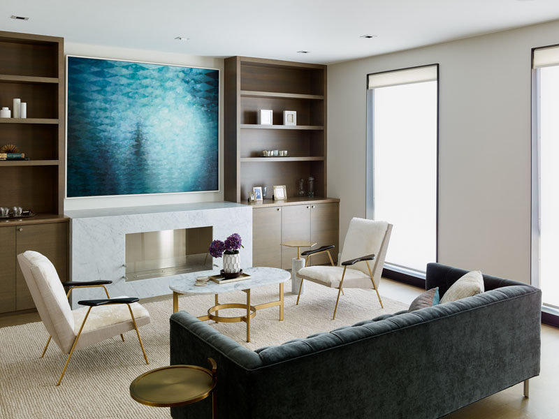 This contemporary living room has built-in wood cabinetry that sits beside the fireplace. #LivingRoom #Shelving