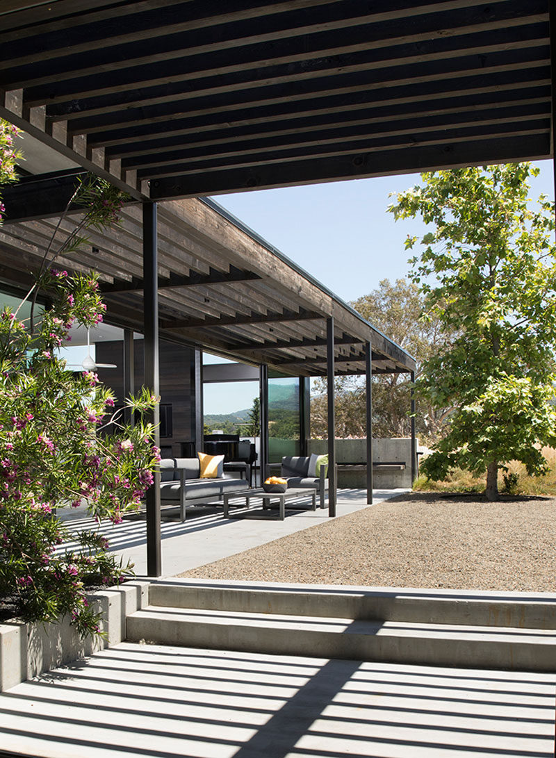 A pergola follows this modern house's L-shaped layout, creating shade for the outdoor lounge. #Pergola #ModernHouse