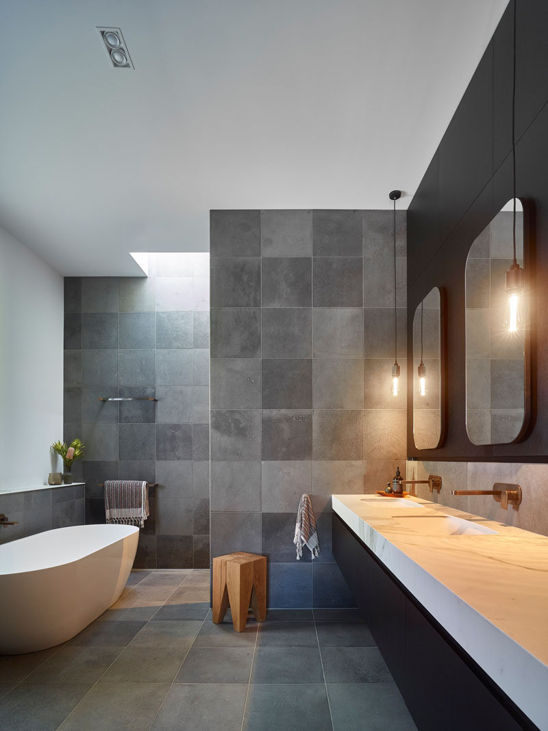 This modern bathroom features a black, white and grey color palette, with a walk-in shower, a freestanding bathtub, and a large dual-sink vanity that sits below two mirrors with pendant lights either side. #BathroomDesign #ModermBathroom