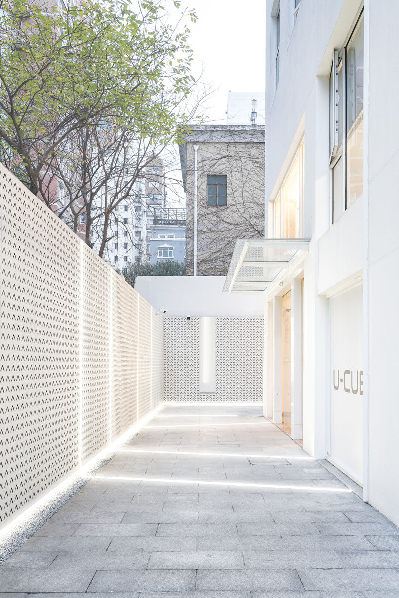To brighten up an alleyway, lighting runs from the building, across the ground, and up onto a decorative fence. #Lighting #BuildingDesign