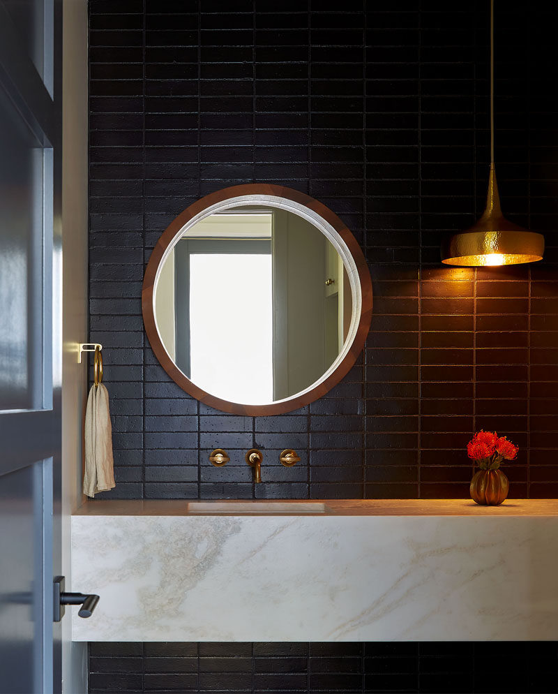 In this bathroom, dramatic dark subway tiles provide a strong contrast to the light-colored vanity and hanging pendant light. #ModernBathroom #DarkTiles