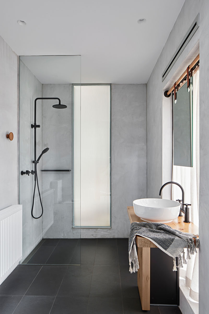 In this modern bathroom, a mirror in front of the window hangs from straps attached to a wood rod, while a floor-to-ceiling glass shower screen separates the shower from the rest of the bathroom. #ModernBathroom #BathroomDesign