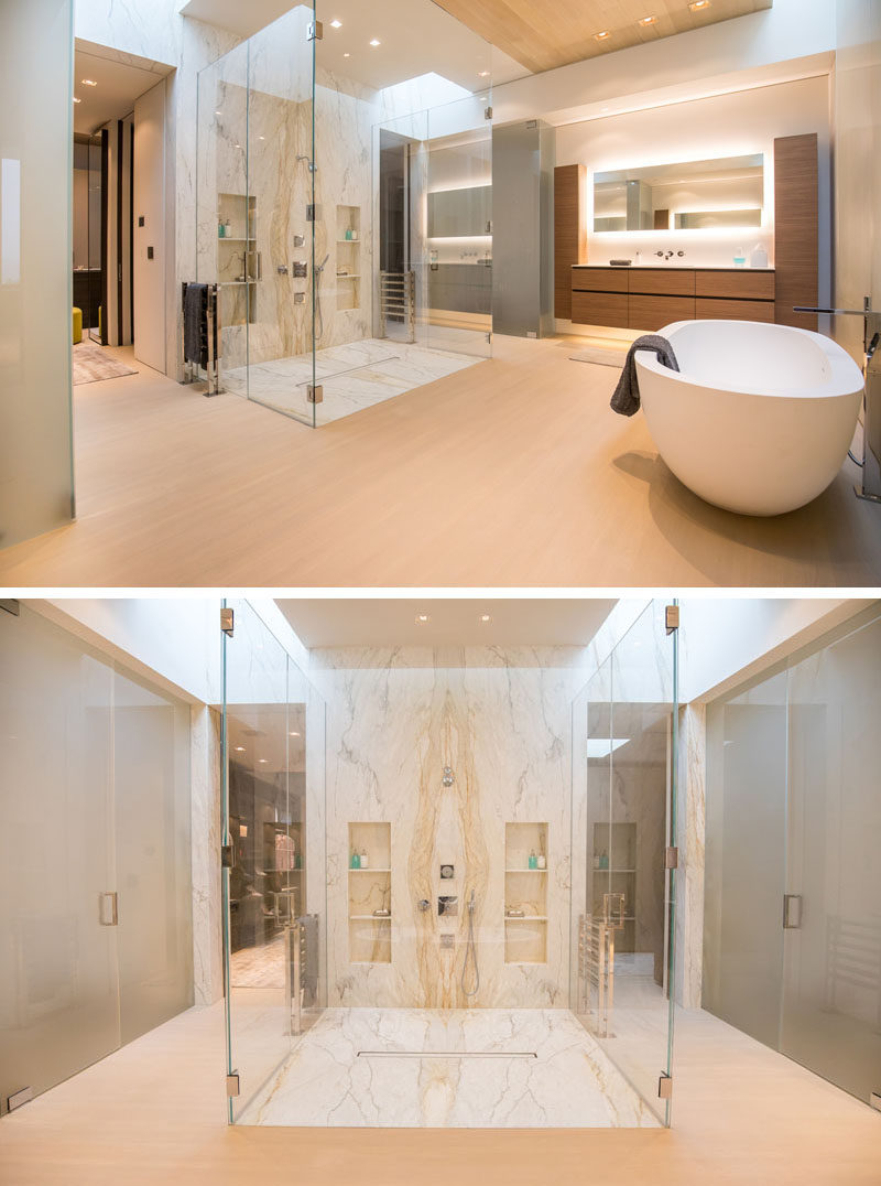 In this modern master bathroom, there's a large walk-in shower with a glass surround, while sitting adjacent to the shower is a freestanding bathtub, and a vanity with a back-lit mirror. #MasterBathroom #GlassEnclosedShower #BathroomDesign
