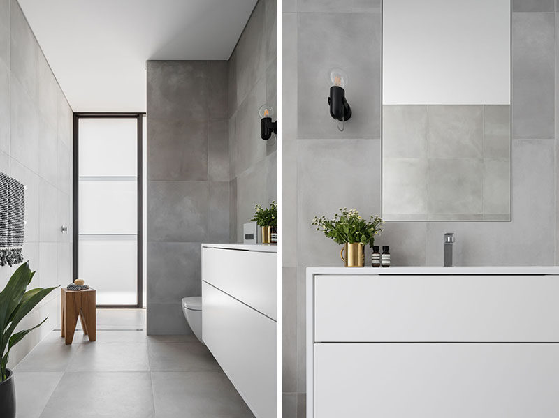 In this bathroom, a simple grey and white color palette has been used for a modern and calming appearance. #ModernBathroom #BathroomDesign