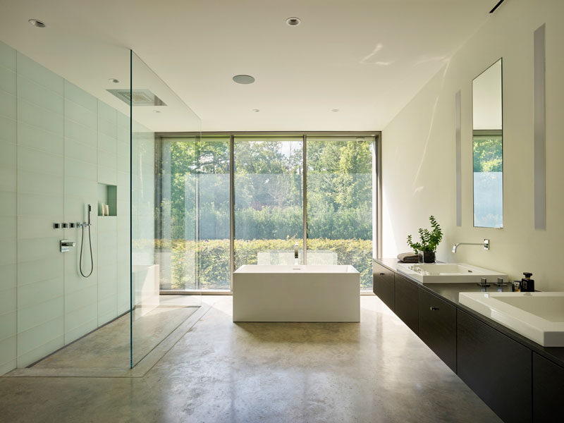 In this modern master bathroom, a large glass enclosed shower sits beside a freestanding bathtub, both of which can enjoy garden views. #ModernBathroom #BathroomDesign