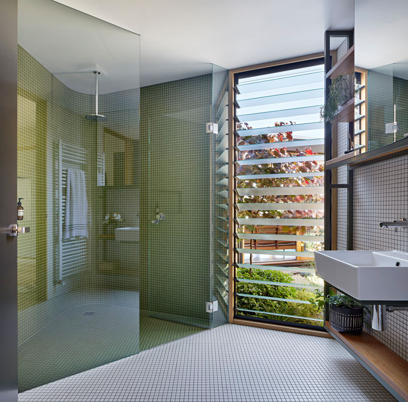 This modern bathroom has louvre windows, and a glass enclosed shower with a curved wall that's covered in small green tiles. #BathroomDesign #GreenTiles #ModernBathroom