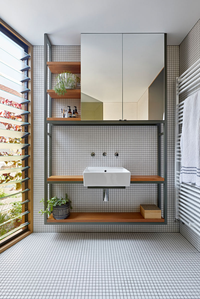 In this modern bathroom, a shelving unit with a mirror and wood shelves, sits beside louvre windows. #ModernBathroom #BathroomVanity